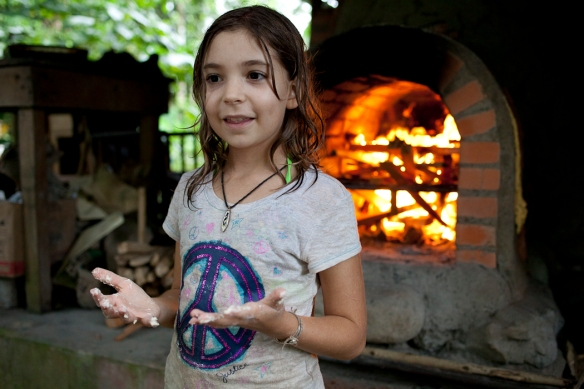 Liv, her hands sticky from making empanadas, stands in front of the Rancho's wood burning stove
