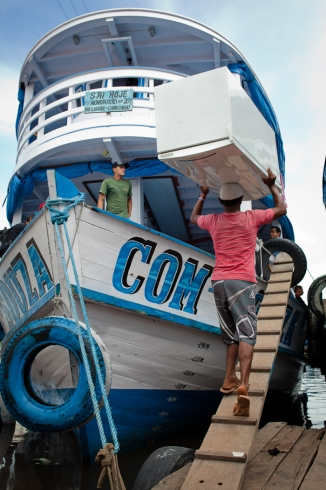 A dock worker carrying a refrigerator onto a river boat in the port of Manaus.