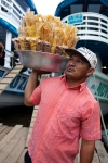 A man selling dried bananas and popcorn to passengers on the river boats.