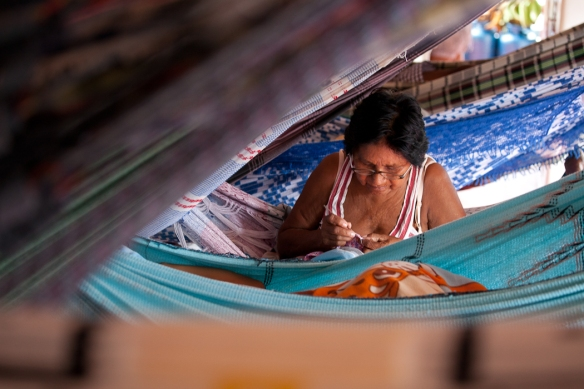 A woman crocheting in her hammock on the Genesis.