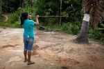 An Indian teenager practicing hitting a target with a traditional blow dart.