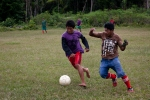 """Two men from the Dow community playing soccer, Instead of dividing teams by """"skins and shirts"""" as is commonly done in the states when no uniforms are available, it seemed they divided by shoes and shoeless (ouch!)"""