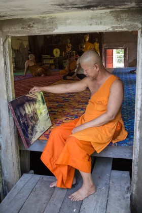 One of the monks looking at a photo of the temple being flooded during a recent storm.