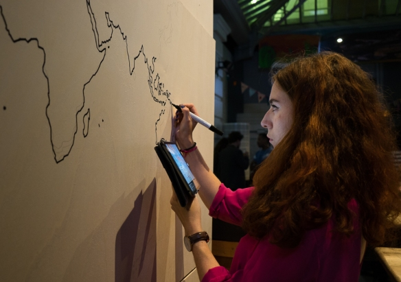 One of the creative organizers of Place to B, drawing a map of the world on the wall.